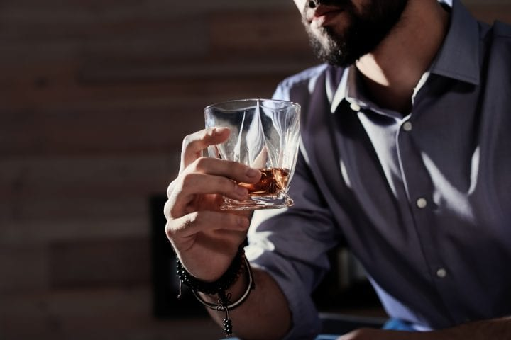Man with glass of whiskey at home, closeup. Space for text