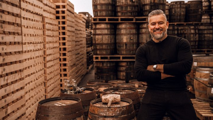 Jay Bradley Whiskey Wealth Club Co-founder in front of barrels